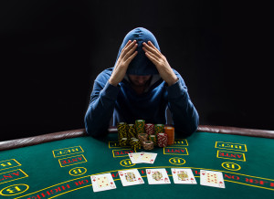 Portrait of a professional poker player sitting at a poker table with poker chips trying to hide his expressions